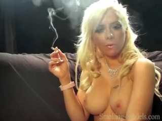 The busty blonde girl touches her sexy big tits and smokes a cigarette.